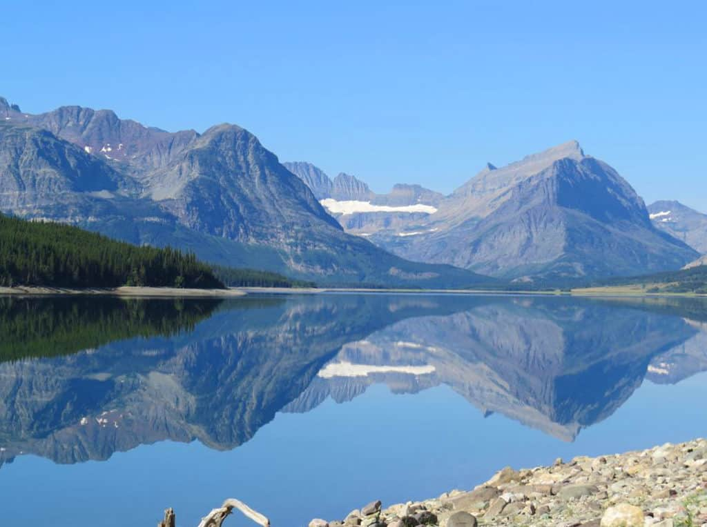 Reflections on Lake Sherburne. Glacier National Park Itinerary: A complete and illustrated day-by-day itinerary for visiting the most beautiful national park in the US!