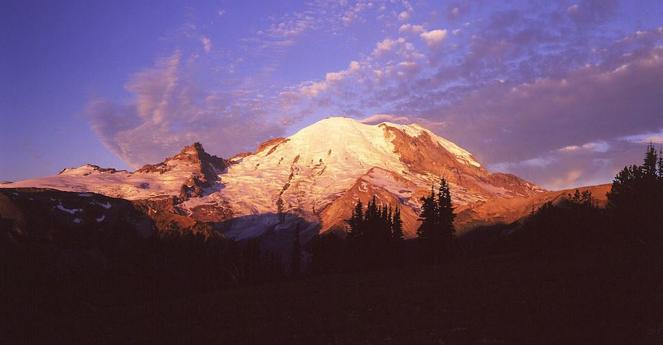 The first rays of morning sun on Mount Rainier, as seen from Sunrise.