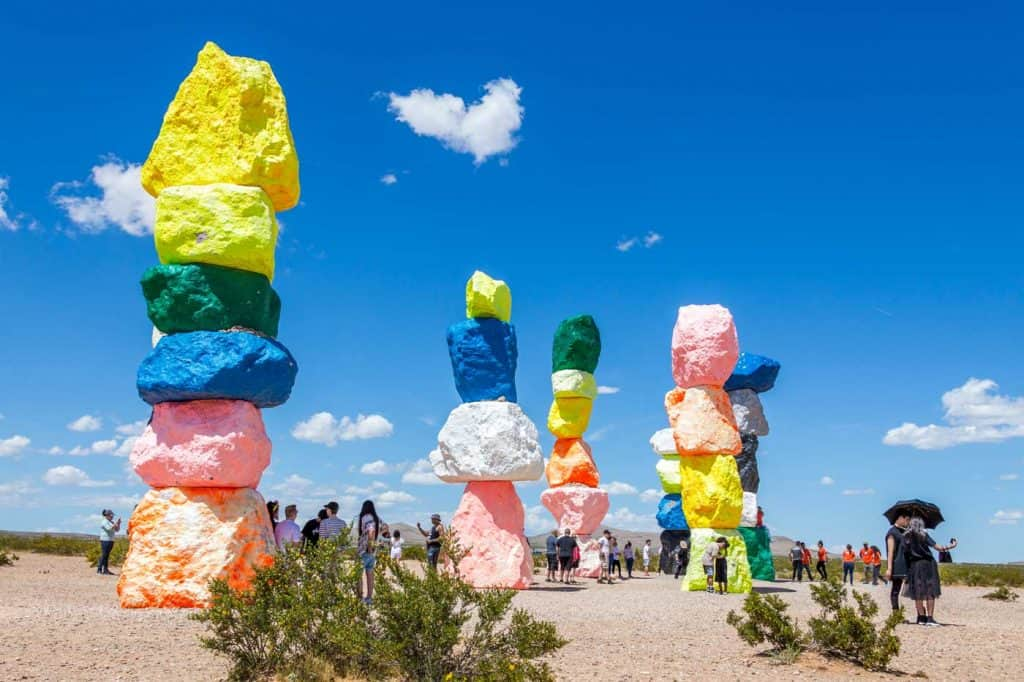 Seven Magic Mountains art installation near Las Vegas city. Pillars made of neon colored boulders stand against barren desert background and blue sky.