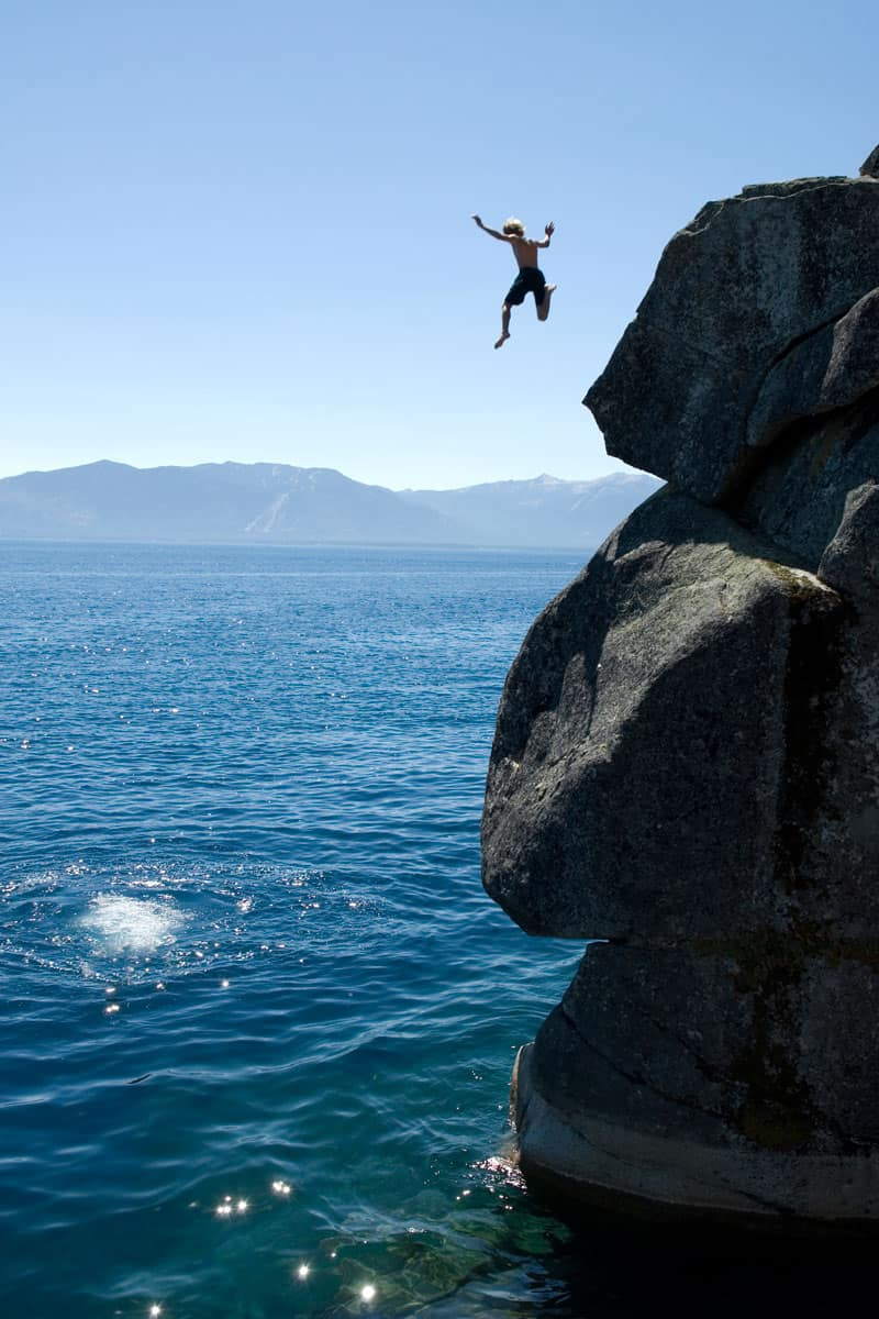 A-young-man-leaps-off-a-cliff-at-Lake-Tahoe