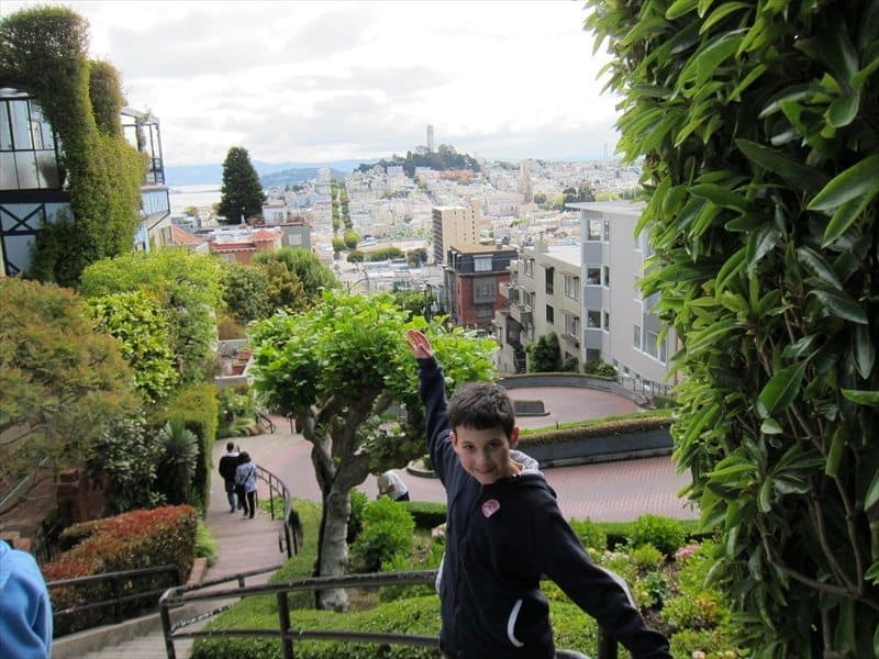 A young boy taking picture at a scenic view of San Francisco