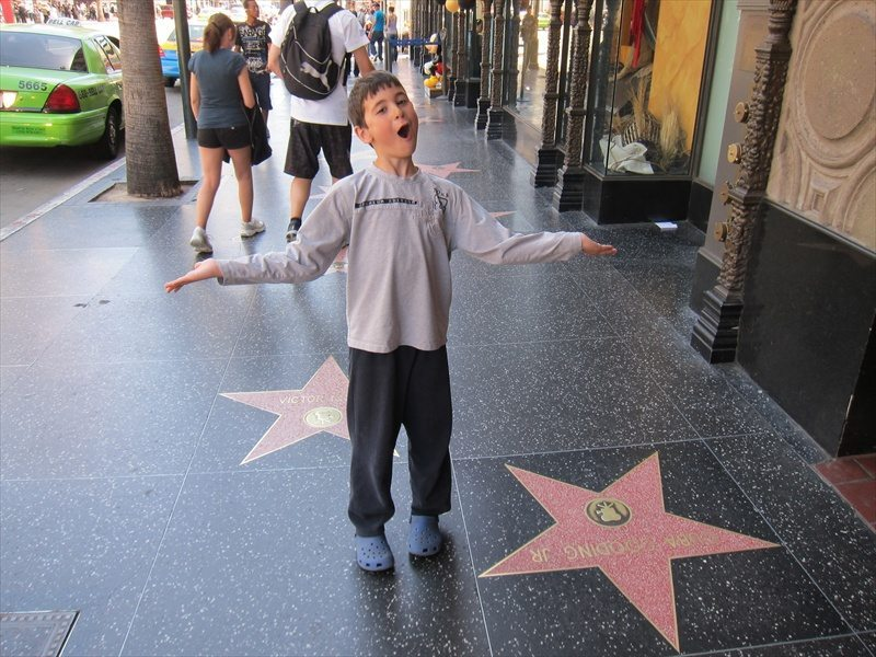 Young kid standing at one of the stars in Hollywoods Walk of Fame