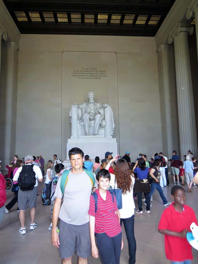 Father holding his son while posing in the Lincoln Memorial Statue