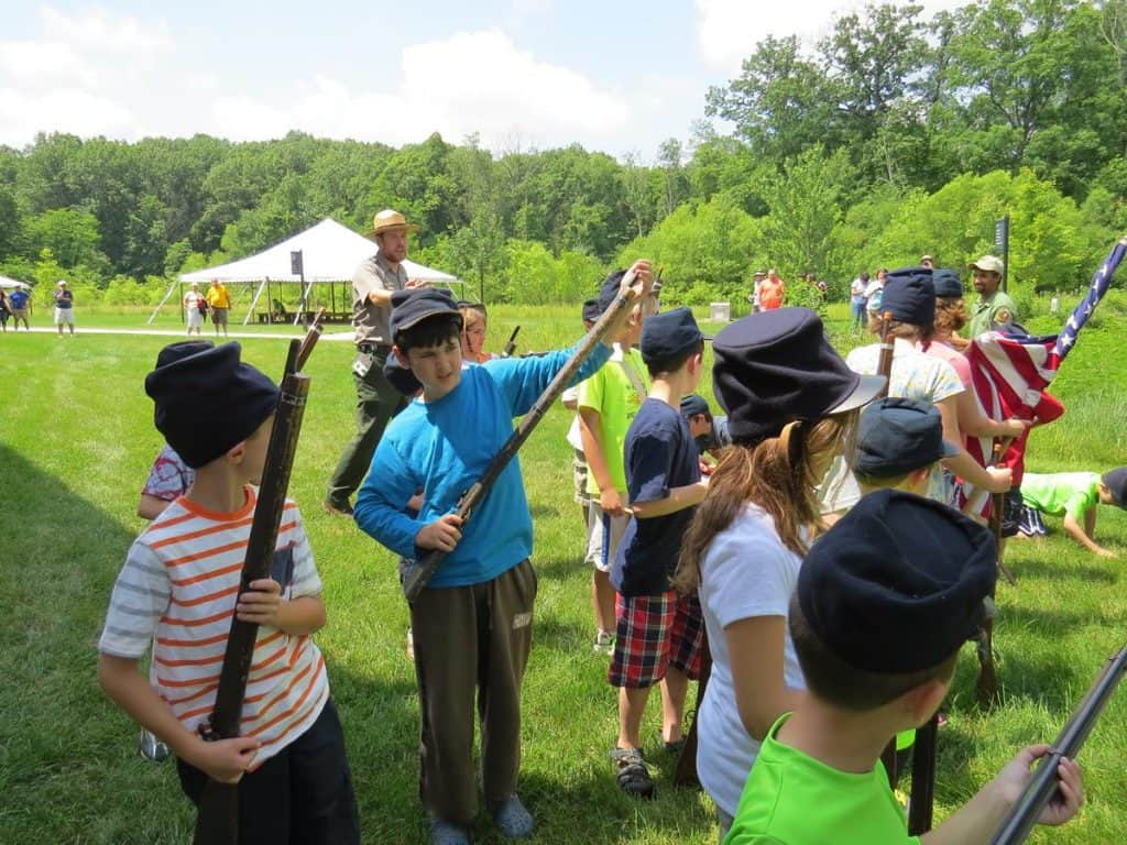 Kids holding toy guns with the instructor behind them at a Jr. Ranger activity at Gettysburg