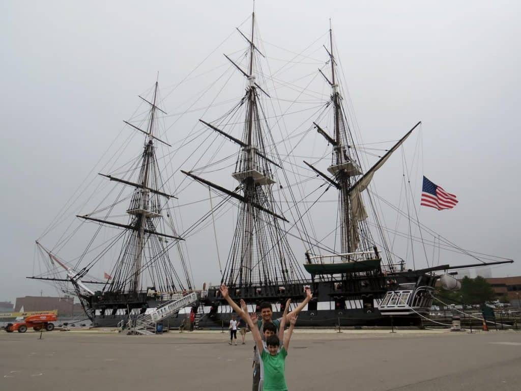 Father happily raising their arms while taking a picture with the USS Constitution