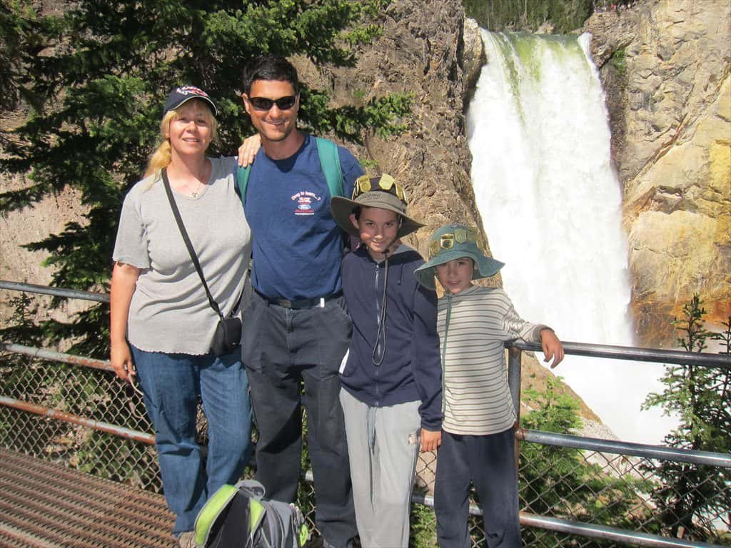 Happy family taking a picture with a beautiful waterfall behind