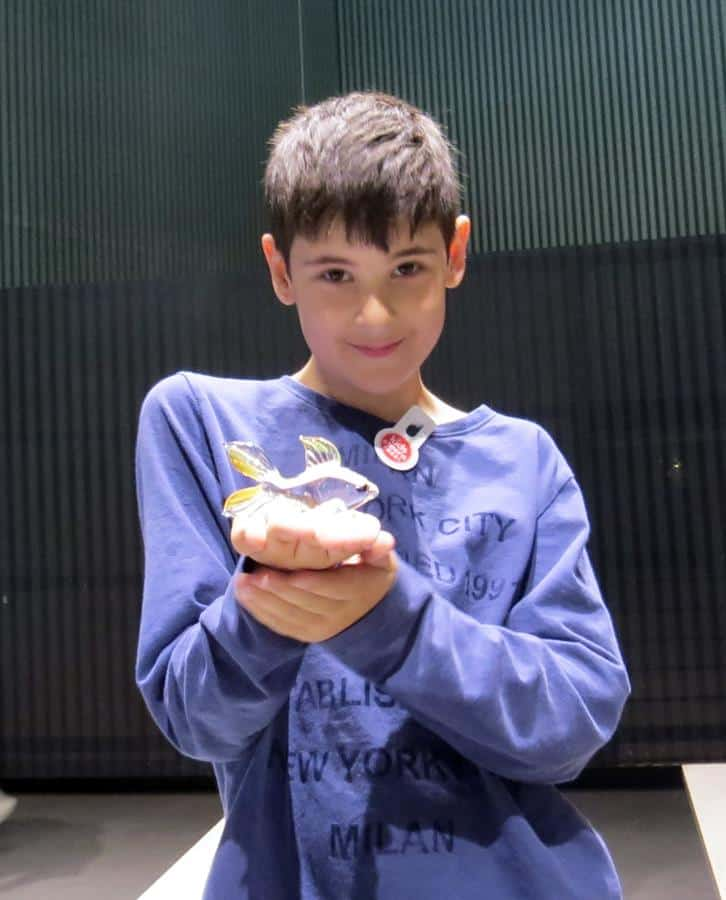 A young boy holding a glass goldfish at Glass Museum