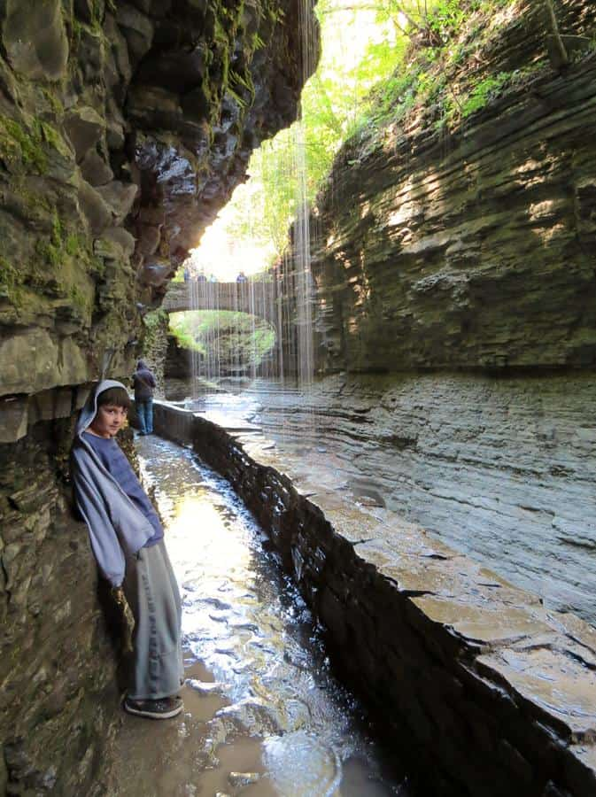 Beautiful hiking trail at Watkins Glen with a cute kid lying his back at rocky wall