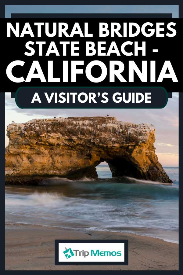 Sunset visual of the iconic rock arch at Natural Bridges State Beach, surrounded by a crashing wave