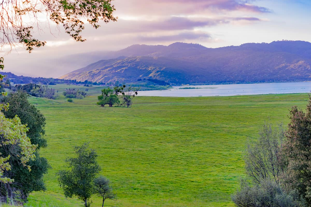 Wide green pasture and tall mountains in Palomar mountains, California