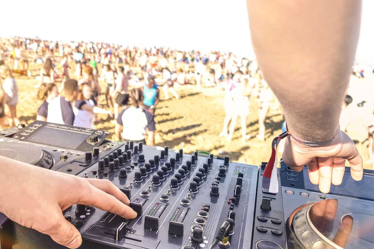 Close up of dj playing electro sound on modern cd usb player at summer beach party - Music festival event and entertainment concept with dancing people
