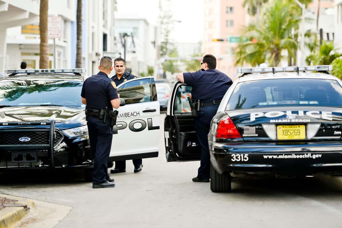 Miami Beach Policemen talking on the street, standing near their cars
