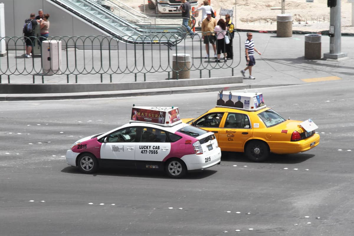 Two cabs ride side by side through an intersection on the Las Vegas Strip