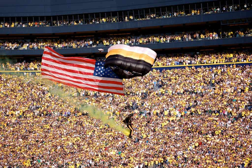 An Airborne parachutish carrying the American flag heading for center field